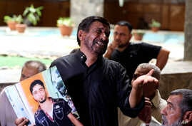 A grieving Iraqi father shows a poster of his dead son, who was an Iraqi soldier, in a Baghdad courtroom, July 8, 2014.