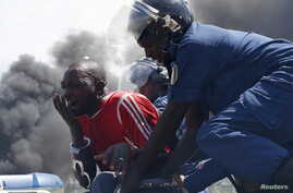 A detained protester cries in front of a burning barricade during a protest against President Pierre Nkurunziza's decision to run for a third term in Bujumbura, Burundi May 13, 2015. A Burundi army general said on Wednesday he had sacked Pierre Nkuru