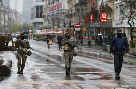 Belgian soldiers and a police officer patrol in central Brussels after security was tightened in Belgium following the fatal attacks in Paris, Nov. 21, 2015.