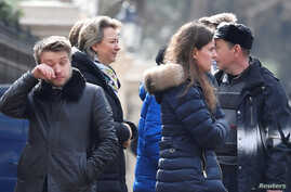 Embassy staff react as colleagues and children board buses outside Russia's Embassy in London, Britain, March 20, 2018.