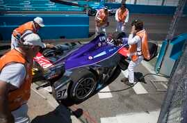 Course officials remove the (37) DS Virgin car driven by Alex Lynn off the track after coming to a stop during Formula E New York City ePrix all-electric auto race Sunday, July 16, 2017, in the Brooklyn borough of New York.
