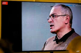 Mikhail Khodorkovsky, once Russia's richest man, speaks during a webcast conference in London, and is seen on a TV screen in Open Russia movement office in Moscow, Dec. 9, 2015.