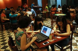 Three young Vietnamese girls use a laptop and smart phones to go online at a cafe in Ha Noi, Vietnam, May 14, 2013.