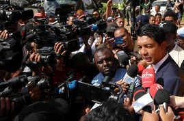 Presidential candidate Andry Rajoelina (R) speaks to journalist after casting his vote in Antananarivo, Madagascar, Dec. 19, 2018.