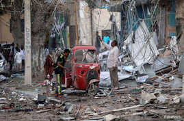 People stand on the rubble of buildings damaged when a suicide car bomb exploded, targeting a Mogadishu hotel in a business center in Maka al-Mukaram street, Mogadishu, Somalia, March 1, 2019.