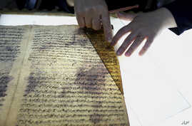 A member of the library restoration staff works on a damaged document at the Baghdad National Library in Iraq, July 28, 2015.