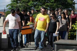 Friends and relatives carry the coffin with the body of Vale SA employee Janice Helena do Nascimento, victim of the collapsed dam, during her burial in Brumadinho, Brazil, Jan. 29, 2019.