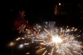 In this Sunday, Oct. 30, 2016 photo, an Indian lights firecrackers to celebrate Diwali, the Hindu festival of lights, in Jammu, India. Hindus across the country are celebrating Diwali where people decorate their homes with light and burst firecracker