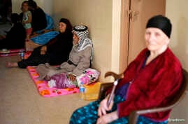 A Christian family, who fled from the violence in Mosul two days ago, stays at a school in Arbil, in Iraq's Kurdistan region, June 27, 2014.