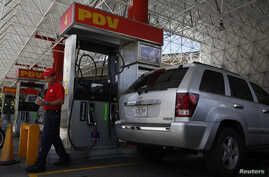 A worker walks next to a fuel dispenser at a gas station, in Caracas, Venezuela, August 29, 2014.