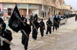 This undated file image posted on a militant website on Tuesday, Jan. 14, 2014 shows fighters from the al-Qaida linked Islamic State of Iraq and the Levant (ISIL) marching in Raqqa, Syria