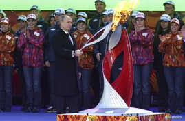 Russian President Vladimir Putin holds a lighted Olympic torch during a ceremony to mark the start of the Sochi Winter Olympic torch relay, in Moscow October 6, 2013.