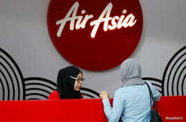 FILE - An AirAsia counter staff attends to a customer at Kuala Lumpur International Airport, Malaysia, Aug. 28, 2016.