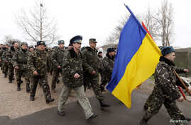 Ukrainian servicemen march away, after negotiations with Russian troops at the Belbek Sevastopol International Airport in the Crimea region, March 4, 2014.