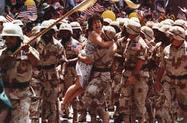 FILE - After breaking through police lines, Debi Kahn, of New Jersey, jumps into the arms of a returning Gulf War veteran during New York's Welcome Home Parade, June 11, 1991.