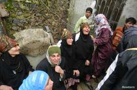 Relatives mourn Ikrama Abkour, whom activists say was killed in a Syrian Air Force missile attack, near Homs, Dec. 21, 2012.