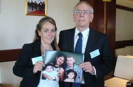 Melissa Rhodes-Smith and Geoff Rhodes hold a photo of Gavin Rhodes and his wife, Phoumalaysy and their children, in Vientiane, Laos, Nov. 28, 2014. (Ron Corben/VOA)