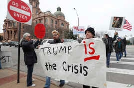 Carolyn Hursh, right, and Joey Daniel, carry a sign during a protest with others in downtown Fort Worth, Texas, Feb. 18, 2019. People gathered on the Presidents Day holiday to protest President Donald Trump's recent national emergency declaration.