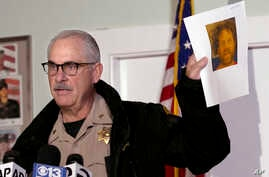 Phil Johnston, the assistant sheriff for Tehama County, Calif., displays a booking photo, from a prior arrest, of Kevin Janson Neal, during a news conference, Nov. 15, 2017, in Rancho Tehama Reserve, Calif. Neal went on a shooting spree Tuesday, kill