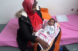 Somali migrant mother Rahma Abukar Ali holds her baby daughter, Sophia, at a refugee center in a small German town near Duesseldorf, where she is awaiting a response to her application for asylum, Oct. 2015. (A. Osman/VOA)