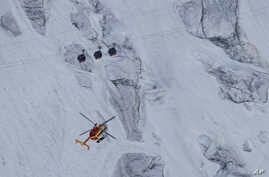 An EC-135 helicopter operated by the French Societe' Civile hovers near three cars of the Panoramic Mont Blanc cable car, Friday, Sept. 9, 2016.