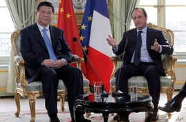FILE- French President Francois Hollande, right, addresses Chinese President Xi Jinping during a meeting at the Elysee Palace in Paris, France, March 26, 2014.