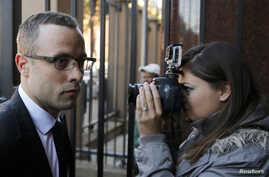 Olympic and Paralympic track star Oscar Pistorius (L) arrives ahead of his trial for the murder of his girlfriend Reeva Steenkamp, at the North Gauteng High Court in Pretoria, May 13, 2014.