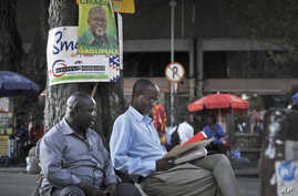 Tanzanians sit next to a tree, underneath an election poster for ruling party presidential candidate John Magufuli, as they await election results in Dar es Salaam, Tanzania, Oct. 27, 2015.