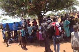 South Sudanese wait in line to register as refugees in Uganda after arriving at Ayilo refugee resettlement camp.
