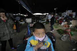 A child wears a mask near the closed poultry section at the Huhai agricultural market where the H7N9 bird flu was detected by authority in Shanghai, China, Apr. 9, 2013.