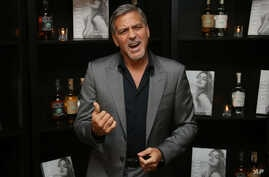 FILE - Actor George Clooney poses for photographs on arrival at the book launch of Cindy Crawford and his own Tequila launch, at the Beaumont Hotel in central London, Oct. 1, 2015