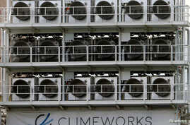 FILE - A facility for capturing CO2 from air of Swiss Climeworks AG is placed on the roof of a waste incinerating plant in Hinwil, Switzerland, July 18, 2017.