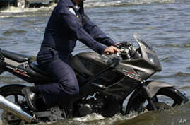 An Air Force officer rides his motorcycle through a flooded Paholyothin road near Don Muang airport in Bangkok, Thailand, October 25, 2011.