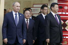 (L-R) Russian President Vladimir Putin, Mongolian President Tsakhia Elbegdorj and Chinese President Xi Jinping arrive for a meeting during the BRICS Summit in Ufa, Russia, July 9, 2015.