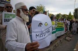 FILE - Pakistanis attend a rally to demand information about missing people who were reportedly picked up by security agencies during anti-al-Qaida raids, in Islamabad, Pakistan, Aug. 30, 2017. Scores of family members of the missing families joined