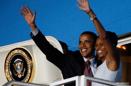 U.S. President Barack Obama and first lady Michelle Obama wave from Air Force One at the airport in Accra, July 11, 2009.