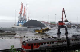 FILE - In this July 24, 2016, file photo, coal brought from Siberia is seen awaiting loading onto a ship bound for China in the North Korean special economic zone of Rason. China has long been the North Korea's main trading partner and diplomatic pro