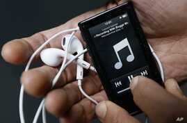 A photo illustration shows a digital music player held in London, Feb. 26, 2013.