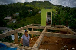 Alma Morales Rosario poses for a portrait between the beams of her home being rebuilt after it was destroyed by Hurricane Maria one year ago in the San Lorenzo neighborhood of Morovis, Puerto Rico, Sept. 8, 2018.