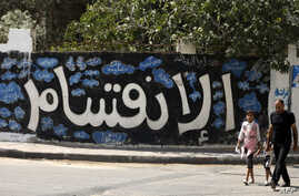 A Palestinian man and his daughter walk past a graffiti reading in Arabic ''Division'' in Gaza City, on Sept. 17, 2017, after Hamas announced it had agreed to steps toward resolving a decade-long split with the Fatah movement.