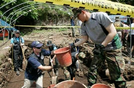 Bob Wood, Garden Valley, Calif., a members of the JPAC, Joint POW/MIA Accounting Command, second from left, deliveries a basket containing earth to South Korean Army soldiers Lee Byung-jin as he digs to search for remains of U.S. soldiers killed duri...