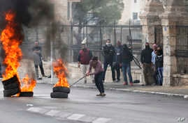 A Palestinian protester pushes a burning tire during a demonstration in the West Bank city of Bethlehem, Dec. 22, 2017.
