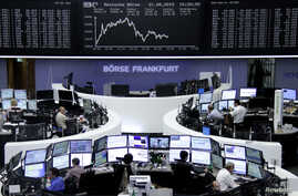 FILE - Traders are pictured at their desks in front of the DAX board at the stock exchange in Frankfurt, Germany, Aug. 21, 2015.