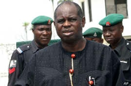 Bayelsa State Governor Diepreye Alamieyeseigha, centre, stands outside his house guarded by policemen in Yenagoa, Nigeria, in this file photo dated November 27, 2005.