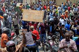Protesters march with placards as they call for reforms during an anti-government rally in Lome, Togo, Sept. 6, 2017.