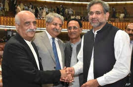 Newly-elected Prime Minister of Pakistan Shahid Khaqan Abbasi, right, is greeted by the Opposition leader Khursheed Shah, left, and others at the Parliament in Islamabad, Pakistan, Tuesday, Aug. 1, 2017.