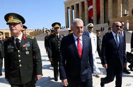 Turkish Prime Minister Binali Yildirim, center, walks with a chief of general staff General Hulusi Akar at Ataturk's mausoleum in Akara, July 28, 2016.