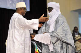Mali's President Ibrahim Boubacar Keita (L) embraces Tuareg rebel coalition representative Mahamadou Djery Maiga on June 20, 2015, in Bamako.