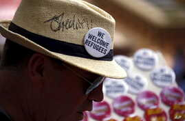 FILE - A man sells badges to demonstrators during a rally in support of refugees that was part of a national campaign in central Sydney, Australia, Oct. 11, 2015.