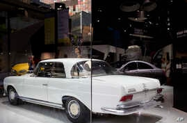 FILE - In this Sept. 23, 2015, photo, models pose next to Mercedes-Benz car models on display during a promotional event at a shopping mall in Beijing. Mercedes-Benz issued an apology in China on Feb. 6, 2018 for quoting the Dalai Lama,